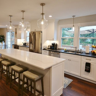 Photo of an expansive transitional u-shaped eat-in kitchen in Philadelphia with an undermount sink, recessed-panel cabinets, white cabinets, quartz benchtops, white splashback, subway tile splashback, stainless steel appliances, vinyl floors, with island, brown floor and white benchtop.