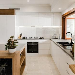 Modern inredning av ett stort grå grått kök, med en dubbel diskho, granitbänkskiva, vitt stänkskydd, stänkskydd i tunnelbanekakel, vita vitvaror, en köksö, beiget golv, släta luckor, vita skåp och klinkergolv i porslin