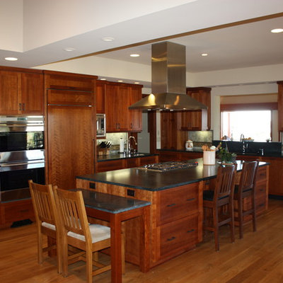 Example of a large arts and crafts l-shaped medium tone wood floor and brown floor eat-in kitchen design in San Diego with an undermount sink, shaker cabinets, dark wood cabinets, granite countertops, multicolored backsplash, porcelain backsplash, paneled appliances, an island and black countertops