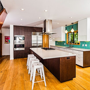 Design ideas for a large midcentury galley eat-in kitchen in San Diego with a single-bowl sink, flat-panel cabinets, dark wood cabinets, quartz benchtops, blue splashback, glass tile splashback, stainless steel appliances, light hardwood floors, with island, yellow floor and white benchtop.