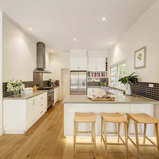 Design ideas for a traditional l-shaped eat-in kitchen in Melbourne with an undermount sink, white cabinets, granite benchtops, ceramic splashback and stainless steel appliances.