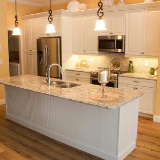 マイアミの中サイズのシャビーシック調のおしゃれなキッチン (アンダーカウンターシンク、シェーカースタイル扉のキャビネット、白いキャビネット、御影石カウンター、ベージュキッチンパネル、石タイルのキッチンパネル、シルバーの調理設備の、無垢フローリング) の写真