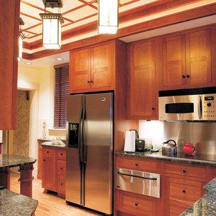 Inspiration för ett avskilt, litet amerikanskt parallellkök, med en undermonterad diskho, skåp i shakerstil, skåp i mellenmörkt trä, granitbänkskiva, vitt stänkskydd, stänkskydd i keramik, rostfria vitvaror, ljust trägolv och en halv köksö