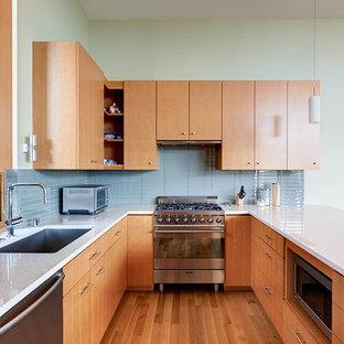 Imagen de cocina actual con fregadero bajoencimera, electrodomésticos de acero inoxidable, armarios con paneles lisos, puertas de armario de madera oscura, salpicadero de azulejos de vidrio y salpicadero azul