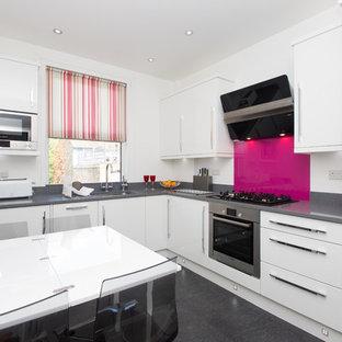 ロンドンの小さいコンテンポラリースタイルのおしゃれなキッチン (アンダーカウンターシンク、フラットパネル扉のキャビネット、白いキャビネット、ピンクのキッチンパネル、珪岩カウンター、ガラス板のキッチンパネル、シルバーの調理設備の、グレーの床) の写真