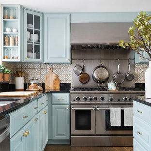 Medium sized traditional l-shaped kitchen/diner in Boston with blue cabinets, terracotta splashback, an island, raised-panel cabinets, multi-coloured splashback, stainless steel appliances, a submerged sink, engineered stone countertops, medium hardwood flooring and brown floors.