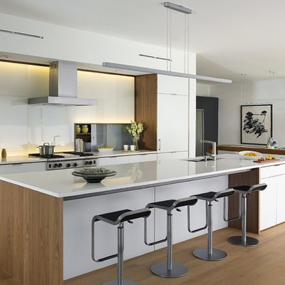 Example of a large trendy galley beige floor and light wood floor eat-in kitchen design in Boston with an undermount sink, flat-panel cabinets, white cabinets, quartz countertops, white backsplash, glass sheet backsplash, paneled appliances, an island and white countertops