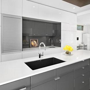 Modelo de cocina minimalista con armarios con paneles lisos, puertas de armario grises, salpicadero verde y salpicadero de vidrio templado