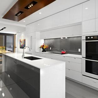 На фото: параллельная кухня в современном стиле с обеденным столом, одинарной раковиной, плоскими фасадами, белыми фасадами, серым фартуком, фартуком из стекла, техникой под мебельный фасад и белой столешницей с