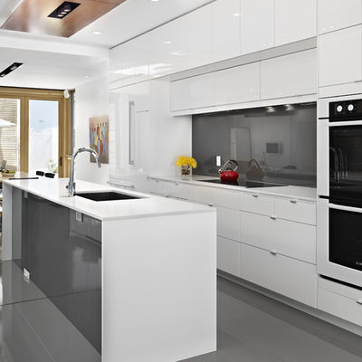 Example of a trendy galley gray floor eat-in kitchen design in Edmonton with an undermount sink, flat-panel cabinets, white cabinets, black backsplash, glass sheet backsplash, white appliances and white countertops