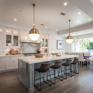 Large traditional eat-in kitchen pictures - Inspiration for a large timeless single-wall brown floor and dark wood floor eat-in kitchen remodel in Los Angeles with a farmhouse sink, shaker cabinets, white backsplash, stainless steel appliances, an island and white cabinets