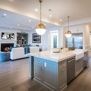 Esempio di una grande cucina classica con lavello stile country, ante in stile shaker, ante grigie, top piastrellato, paraspruzzi bianco, paraspruzzi in gres porcellanato, elettrodomestici in acciaio inossidabile, pavimento in legno massello medio, isola e pavimento marrone