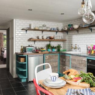 На фото: маленькая угловая кухня в стиле фьюжн с обеденным столом, накладной раковиной, фасадами в стиле шейкер, искусственно-состаренными фасадами, деревянной столешницей, белым фартуком, фартуком из керамической плитки, черной техникой, полом из сланца и серым полом с
