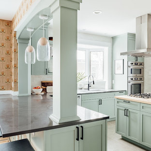 Medium sized traditional l-shaped kitchen/diner in Salt Lake City with shaker cabinets, green cabinets, composite countertops, stainless steel appliances, cement flooring, an island, grey floors, grey worktops, a submerged sink, white splashback and window splashback.