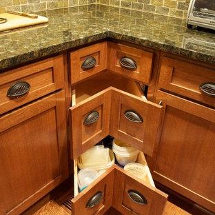 インディアナポリスの中サイズのトラディショナルスタイルのおしゃれなキッチン (エプロンフロントシンク、シェーカースタイル扉のキャビネット、中間色木目調キャビネット、御影石カウンター、緑のキッチンパネル、石タイルのキッチンパネル、シルバーの調理設備の、無垢フローリング) の写真