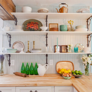 Example of an eclectic single-wall open concept kitchen design in New York with a farmhouse sink, shaker cabinets, white cabinets, wood countertops, gray backsplash and stainless steel appliances