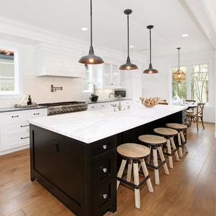 Offene, Zweizeilige Klassische Küche mit Schrankfronten mit vertiefter Füllung, weißen Schränken, Marmor-Arbeitsplatte, Küchenrückwand in Weiß und Rückwand aus Metrofliesen in Orange County