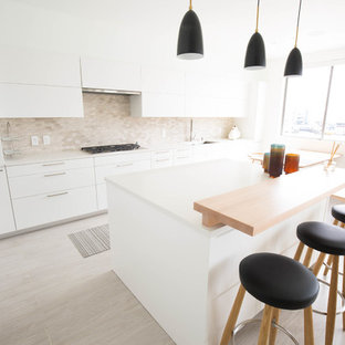 Small contemporary l-shaped eat-in kitchen in Orange County with an undermount sink, flat-panel cabinets, white cabinets, quartz benchtops, grey splashback, marble splashback, stainless steel appliances, porcelain floors, with island, grey floor and yellow benchtop.