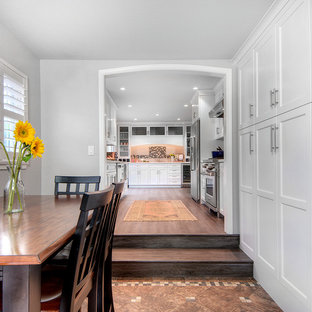Inspiration for a mid-sized transitional galley eat-in kitchen in San Francisco with an undermount sink, shaker cabinets, white cabinets, quartz benchtops, multi-coloured splashback, mosaic tile splashback, stainless steel appliances, vinyl floors, no island, brown floor and white benchtop.
