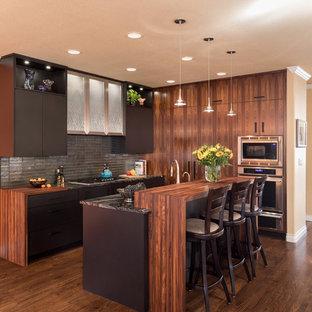 Esempio di una cucina design con ante lisce, ante marroni, paraspruzzi a effetto metallico, elettrodomestici in acciaio inossidabile, parquet scuro, isola e pavimento marrone