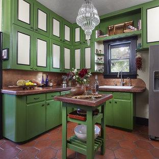 Mediterrane Küche in L-Form mit Einbauwaschbecken, flächenbündigen Schrankfronten, grünen Schränken, Küchenrückwand in Braun, Küchengeräten aus Edelstahl, Terrakottaboden, Kücheninsel, braunem Boden und brauner Arbeitsplatte in Denver