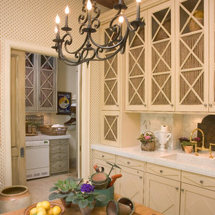 Photo of a traditional kitchen in Other with glass-front cabinets and beige cabinets.