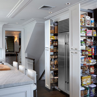 Large transitional l-shaped kitchen pantry in New York with an undermount sink, glass-front cabinets, white cabinets, marble benchtops, white splashback, glass tile splashback, stainless steel appliances, dark hardwood floors and with island.