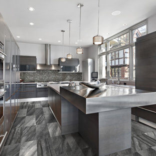 Large contemporary enclosed kitchen photos - Large trendy u-shaped porcelain floor enclosed kitchen photo in Toronto with flat-panel cabinets, stainless steel countertops, metallic backsplash, paneled appliances, an island, dark wood cabinets, glass tile backsplash and an undermount sink