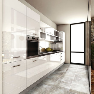 Enclosed kitchen - mid-sized modern galley porcelain floor enclosed kitchen idea in Toronto with an undermount sink, flat-panel cabinets, white cabinets, quartz countertops, white backsplash, porcelain backsplash, stainless steel appliances and no island