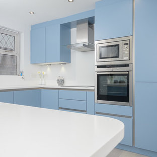 Mid-sized modern l-shaped eat-in kitchen in Other with an integrated sink, flat-panel cabinets, blue cabinets, solid surface benchtops, white splashback, panelled appliances, linoleum floors and a peninsula.