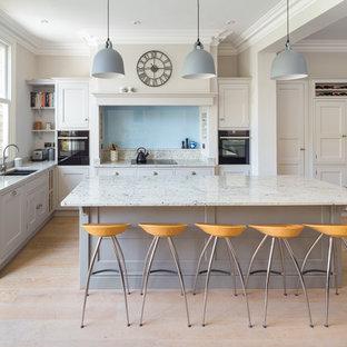 Klassisk inredning av ett stort beige beige kök, med en nedsänkt diskho, skåp i shakerstil, beige skåp, marmorbänkskiva, beige stänkskydd, stänkskydd i marmor, svarta vitvaror, ljust trägolv, en köksö och beiget golv