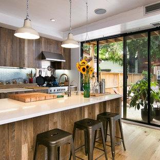 ニューヨークの大きいビーチスタイルのおしゃれなキッチン (中間色木目調キャビネット、クオーツストーンカウンター、青いキッチンパネル、磁器タイルのキッチンパネル、エプロンフロントシンク、シルバーの調理設備の、淡色無垢フローリング) の写真