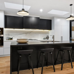 This is an example of a large contemporary galley kitchen in Melbourne with a double-bowl sink, flat-panel cabinets, black cabinets, quartz benchtops, marble splashback, stainless steel appliances, with island, brown floor, black benchtop, white splashback and medium hardwood floors.