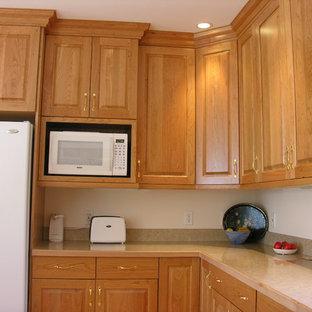 Idéer för stora vintage kök, med en nedsänkt diskho, luckor med upphöjd panel, skåp i mellenmörkt trä, laminatbänkskiva, vita vitvaror, ljust trägolv och en köksö