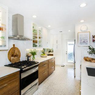 マイアミの中サイズのミッドセンチュリースタイルのおしゃれなキッチン (アンダーカウンターシンク、シェーカースタイル扉のキャビネット、中間色木目調キャビネット、クオーツストーンカウンター、白いキッチンパネル、磁器タイルのキッチンパネル、シルバーの調理設備の、テラゾの床、アイランドなし、マルチカラーの床) の写真