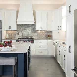 Design ideas for a large traditional l-shaped kitchen pantry in Kansas City with a single-bowl sink, shaker cabinets, white cabinets, engineered stone countertops, grey splashback, stone tiled splashback, stainless steel appliances, porcelain flooring, an island, grey floors and white worktops.