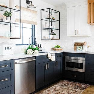 フェニックスの中くらいのトランジショナルスタイルのおしゃれなL型キッチン (アンダーカウンターシンク、シェーカースタイル扉のキャビネット、青いキャビネット、珪岩カウンター、白いキッチンパネル、レンガのキッチンパネル、シルバーの調理設備、淡色無垢フローリング、ベージュの床、白いキッチンカウンター) の写真