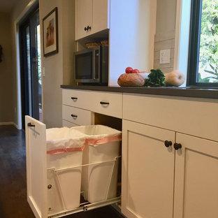 Bild på ett mellanstort vintage brun brunt kök, med en undermonterad diskho, skåp i shakerstil, vita skåp, bänkskiva i kvarts, beige stänkskydd, stänkskydd i tunnelbanekakel, rostfria vitvaror, mellanmörkt trägolv och en köksö