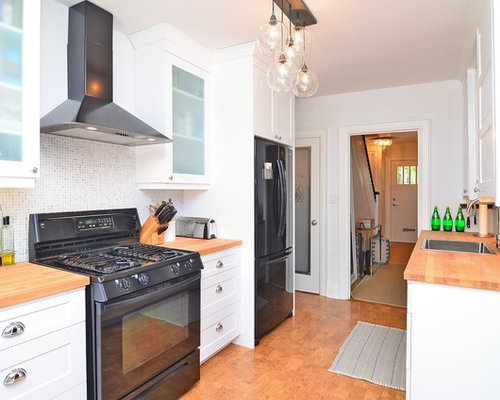 Traditional galley kitchen idea in Toronto with black appliances, wood  countertops, shaker cabinets,