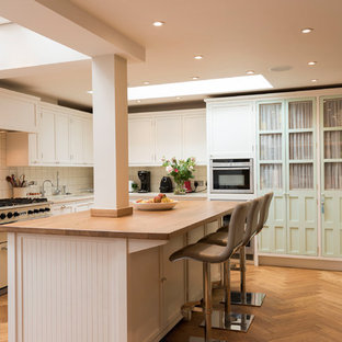 Photo of a large traditional u-shaped kitchen/diner in London with shaker cabinets, white cabinets, wood worktops, white splashback, ceramic splashback, medium hardwood flooring, an island, brown floors, a submerged sink, stainless steel appliances and beige worktops.