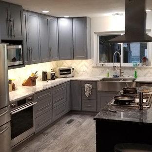 Inspiration för ett mellanstort flerfärgad flerfärgat kök, med en rustik diskho, skåp i shakerstil, grå skåp, granitbänkskiva, stänkskydd i stenkakel, rostfria vitvaror, laminatgolv, en köksö och grått golv