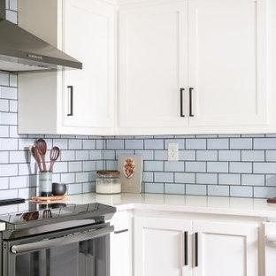 Foto på ett mellanstort vintage vit kök, med en rustik diskho, vita skåp, blått stänkskydd, stänkskydd i keramik, mellanmörkt trägolv och brunt golv