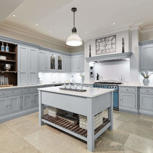Large classic l-shaped kitchen in London with shaker cabinets, blue cabinets, quartz worktops, white splashback, coloured appliances, limestone flooring, an island, multi-coloured floors and white worktops.