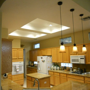 Design ideas for a mid-sized traditional u-shaped eat-in kitchen in Sacramento with a double-bowl sink, shaker cabinets, brown cabinets, granite benchtops, blue splashback, stone slab splashback, white appliances, porcelain floors, a peninsula and beige floor.