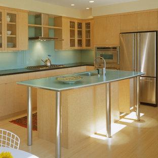 Foto de cocina comedor en L, moderna, de tamaño medio, con fregadero bajoencimera, armarios con paneles lisos, puertas de armario de madera clara, encimera de acrílico, salpicadero azul, salpicadero de vidrio templado, electrodomésticos de acero inoxidable, suelo de bambú y una isla