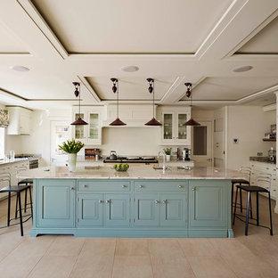 Ejemplo de cocina comedor en U, campestre, con armarios con paneles con relieve, puertas de armario blancas, electrodomésticos de acero inoxidable y una isla
