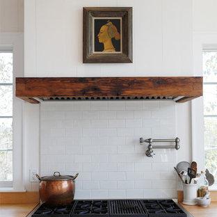 Kitchen - cottage kitchen idea in Philadelphia with white cabinets, wood countertops, white backsplash, subway tile backsplash and stainless steel appliances