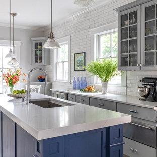 Große Maritime Wohnküche mit Unterbauwaschbecken, grauen Schränken, Quarzwerkstein-Arbeitsplatte, Küchenrückwand in Weiß, Küchengeräten aus Edelstahl, Kücheninsel, weißer Arbeitsplatte, Glasfronten, Rückwand aus Metrofliesen und hellem Holzboden in Boston