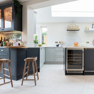 Design ideas for a large scandi galley kitchen/diner in West Midlands with a built-in sink, shaker cabinets, grey cabinets, marble worktops, black appliances, ceramic flooring, an island, white floors and white worktops.