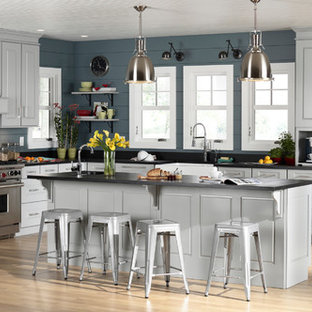 Design ideas for a large contemporary l-shaped separate kitchen in Orange County with with island, grey cabinets, a farmhouse sink, shaker cabinets, solid surface benchtops, stainless steel appliances, light hardwood floors, black splashback, stone slab splashback and beige floor.